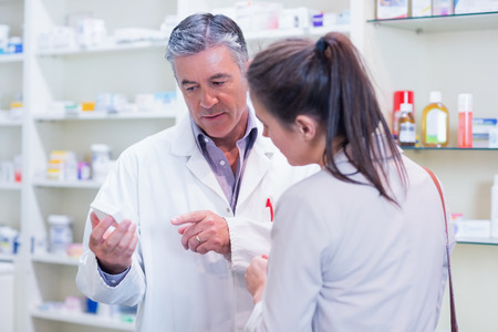 Photo for Pharmacist speaking with cheerful young customer in the pharmacy - Royalty Free Image