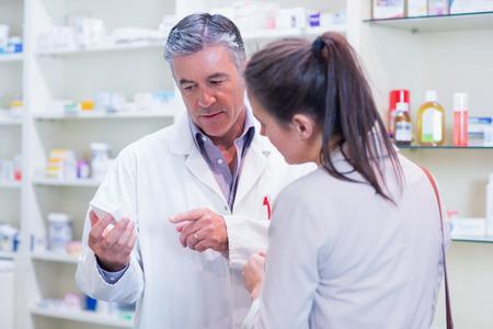 Foto de Pharmacist speaking with cheerful young customer in the pharmacy - Imagen libre de derechos