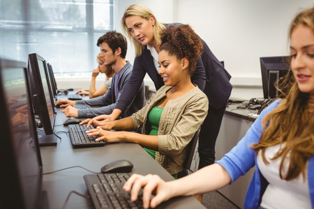 Photo for Attractive teacher helping her student in computer class at the university - Royalty Free Image