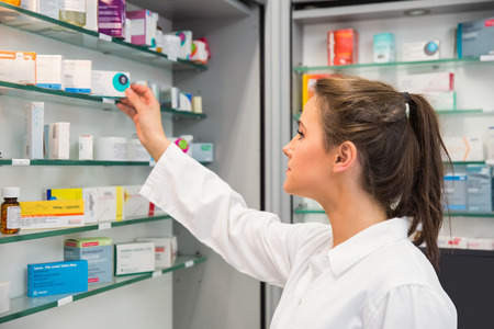 Photo for Junior pharmacist taking medicine from shelf at the hospital pharmacy - Royalty Free Image