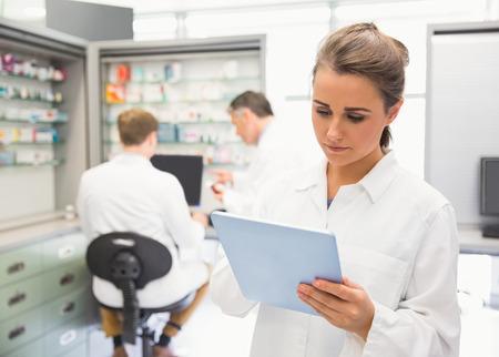 Foto de Junior pharmacist using tablet pc at the hospital pharmacy - Imagen libre de derechos