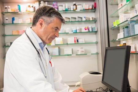 Foto de Focused pharmacist using the computer at the hospital pharmacy - Imagen libre de derechos