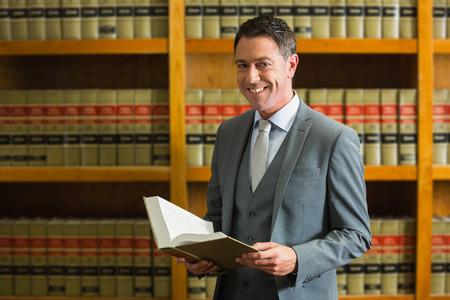 Foto de Lawyer holding book in the law library at the university - Imagen libre de derechos
