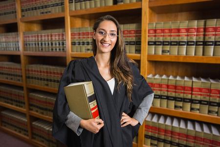 Foto de Pretty lawyer looking at camera in the law library at the university - Imagen libre de derechos