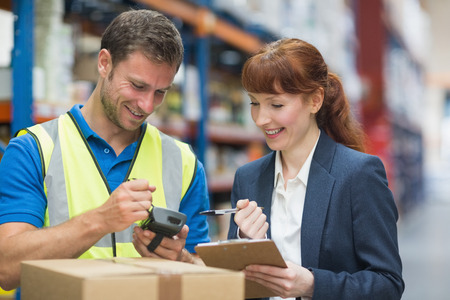 Photo pour Portrait of manual worker and manager scanning package in the warehouse - image libre de droit