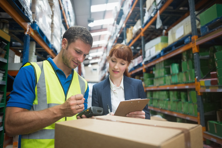 Foto de Portrait of manual worker and manager scanning package in the warehouse - Imagen libre de derechos