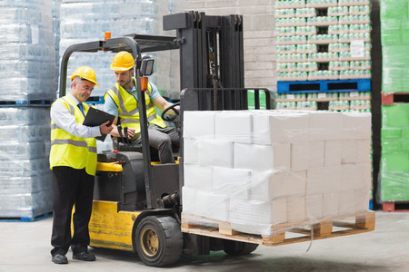 Photo for Forklift driver talking with his manager in a large warehouse - Royalty Free Image
