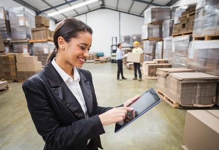 Photo pour Female manager using digital tablet in warehouse - image libre de droit