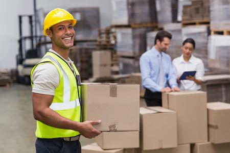 Photo pour Portrait of worker carrying box in the warehouse - image libre de droit