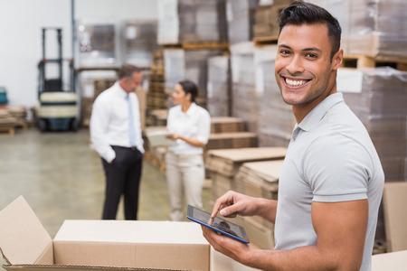 Photo pour Smiling manager using digital tablet in warehouse - image libre de droit