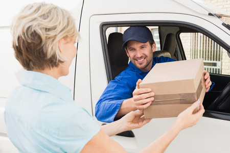 Foto per Delivery driver handing parcel to customer in his van outside the warehouse - Immagine Royalty Free