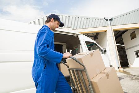 Photo pour Delivery driver packing his van in a large warehouse - image libre de droit