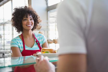 Photo pour Pretty waitress giving sandwich to customer at the bakery - image libre de droit