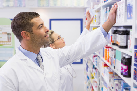 Foto de Team of pharmacists looking at medicine at the hospital pharmacy - Imagen libre de derechos