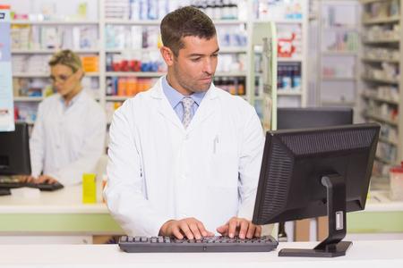 Foto de Concentrate pharmacist using computer at the hospital pharmacy - Imagen libre de derechos