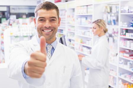 Foto de Happy pharmacist holding his thumb at pharmacy - Imagen libre de derechos