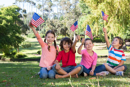 Photo for Happy little friends waving american flag on a sunny day - Royalty Free Image
