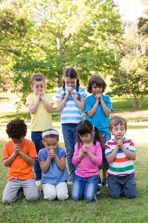 Photo for Children saying their prayers in park on a sunny day - Royalty Free Image