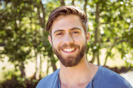 Photo for Handsome hipster smiling at camera on a summers day - Royalty Free Image