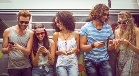 Foto de Hipster friends using their phones on a summers day - Imagen libre de derechos
