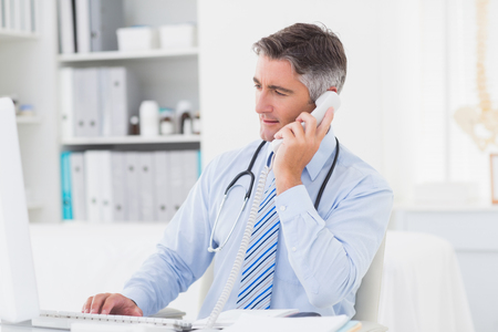 Foto de Male doctor using telephone while working on computer at table in clinic - Imagen libre de derechos