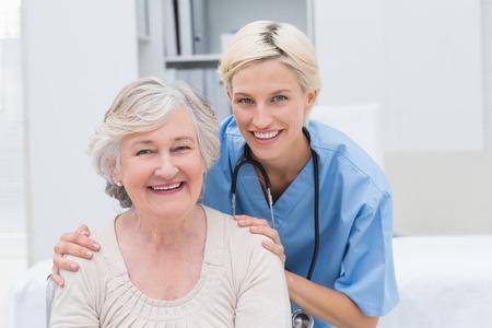 Foto de Portrait of friendly nurse with hands on senior patients shoulders in clinic - Imagen libre de derechos