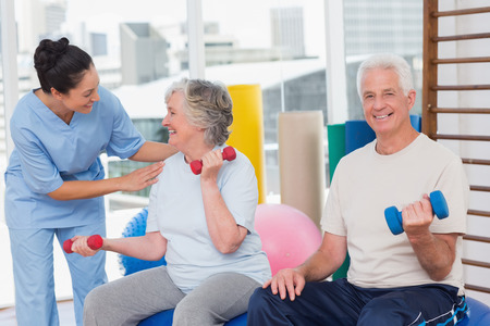 Photo for Happy trainer communicating with senior woman sitting by man in gym - Royalty Free Image