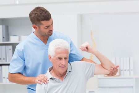 Photo for Physiotherapist giving physical therapy to senior man in clinic - Royalty Free Image
