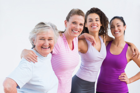 Photo for Portrait of happy friends standing arms around in fitness studio - Royalty Free Image