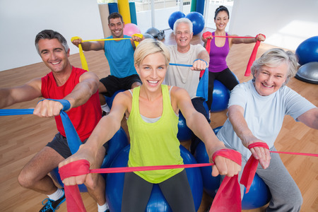 Foto de Portrait of happy men and women on fitness balls exercising with resistance bands in gym class - Imagen libre de derechos