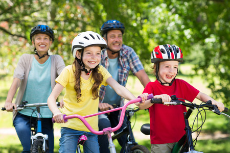 Foto de Happy family on their bike at the park on a sunny day - Imagen libre de derechos
