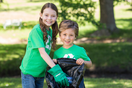 Photo for Happy siblings collecting rubbish on a sunny day - Royalty Free Image