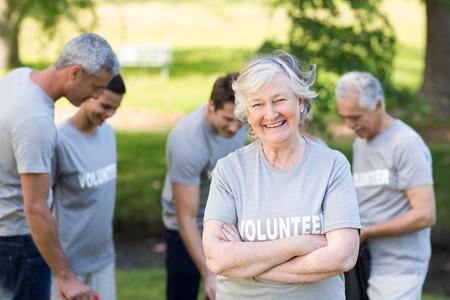 Foto de Happy volunteer grandmother smiling at camera on a sunny day - Imagen libre de derechos