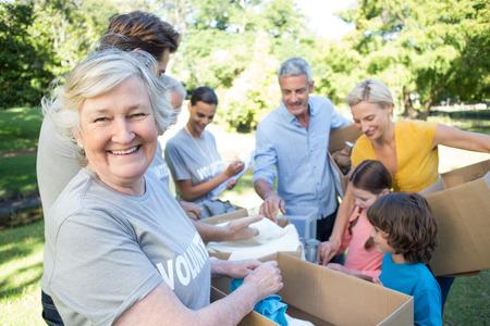 Foto de Happy volunteer family separating donations stuffs on a sunny day - Imagen libre de derechos
