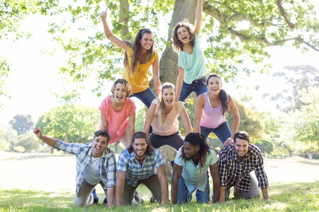 Photo for Happy friends in the park making human pyramid on a sunny day - Royalty Free Image