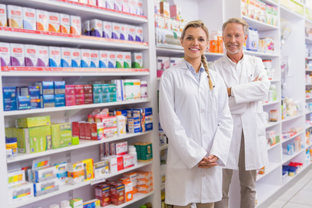 Foto de Pharmacist with his trainee standing and smiling at camera in the pharmacy - Imagen libre de derechos