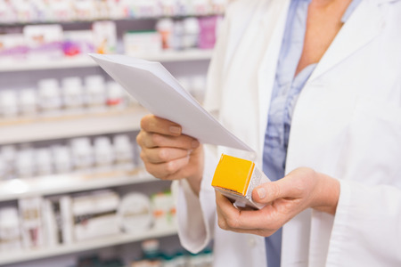 Photo for Pharmacist looking at prescription and medicine in the pharmacy - Royalty Free Image