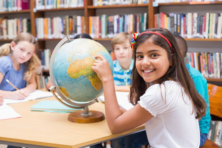 Photo pour Cute pupils looking at globe in library at the elementary school - image libre de droit