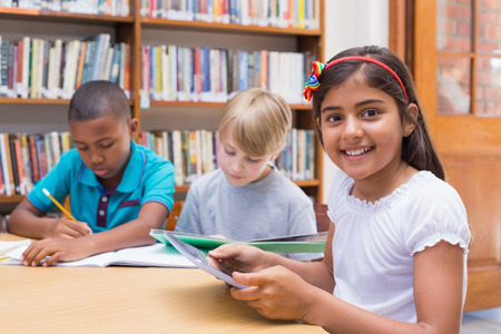 Photo for Cute pupil using tablet computer in library at the elementary school - Royalty Free Image