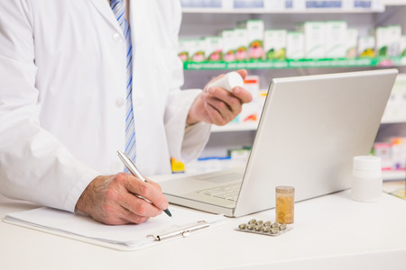 Photo for Pharmacist writing on clipboard and holding medication in the pharmacy - Royalty Free Image
