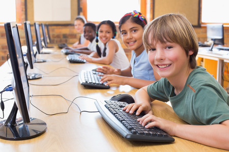 Photo pour Cute pupils in computer class at the elementary school - image libre de droit