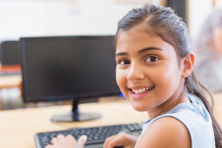 Foto de Cute pupil in computer class at the elementary school - Imagen libre de derechos
