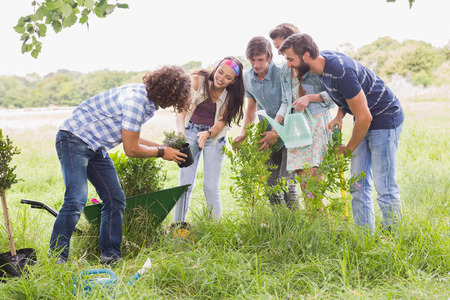 Photo for Happy friends gardening for the community on a sunny day - Royalty Free Image