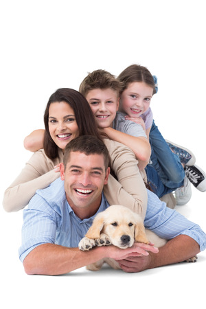 Photo pour Portrait of happy family lying on top of each other with dog over white background - image libre de droit