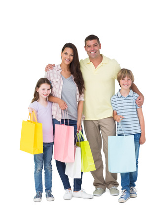 Photo for Portrait of happy family carrying shopping bags over white background - Royalty Free Image