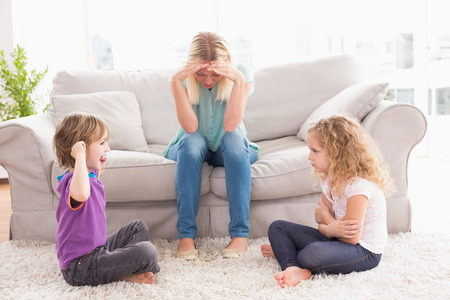 Photo pour Upset woman sitting on sofa while brother teasing sister at home - image libre de droit