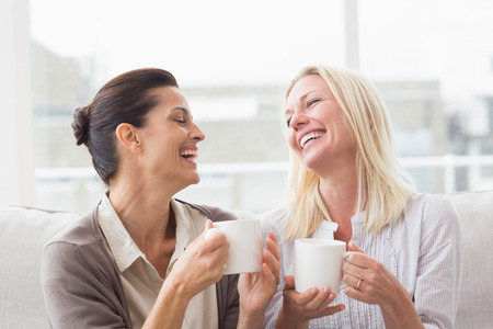 Photo for Cheerful women gossiping while having coffee in living room - Royalty Free Image