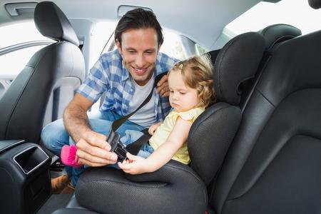 Foto de Father securing baby in the car seat in his car - Imagen libre de derechos