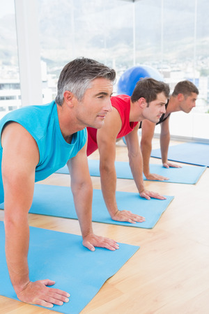 Photo pour Group of men working on exercise mat in fitness studio - image libre de droit