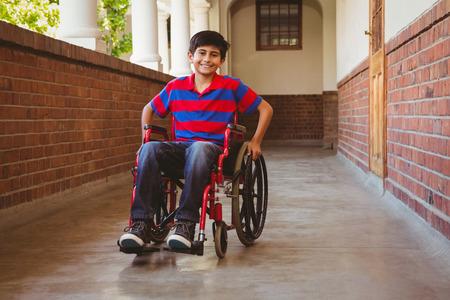 Foto de Portrait of cute little boy sitting in wheelchair in school corridor - Imagen libre de derechos